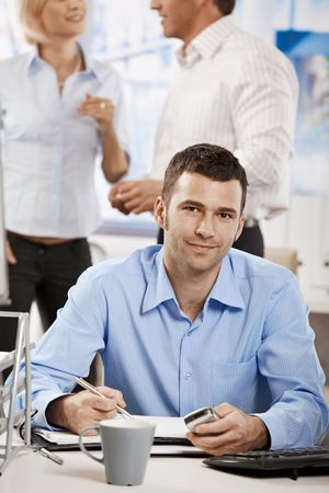 Casual businessman working in office, sitting at desk, writing notes to personal organizer. photo
