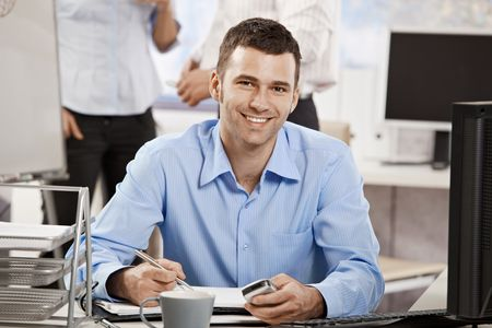Casual young businessman working in office, sitting at desk, writing notes to personal organizer. photo