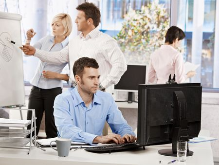 office note: Casual businessman sitting at office desk, working on computer. Businesspeople working in background. Stock Photo