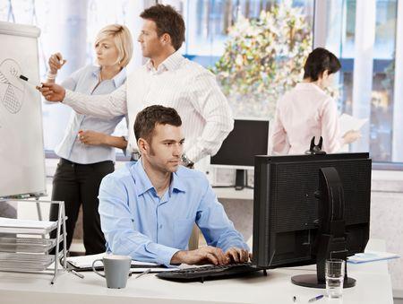 Casual empresario sentado en el escritorio de la Oficina, trabajando en equipo. Empresarios que trabajan en segundo plano.