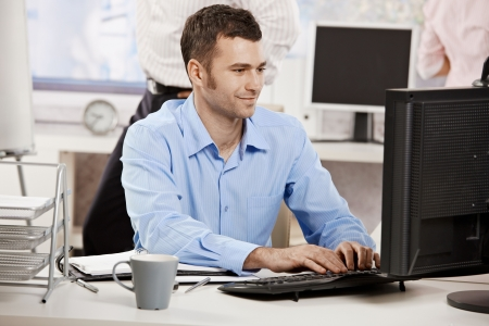 person at computer: Casual businessman working in office, sitting at desk, typing on keyboard, looking at computer screen.