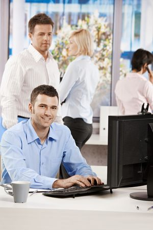 Casual businessman working with computer in office, looking at camera, smiling. photo
