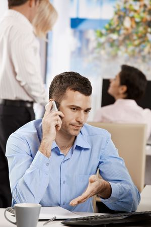 Businessman sitting at desk in office, talking on mobile phone. photo