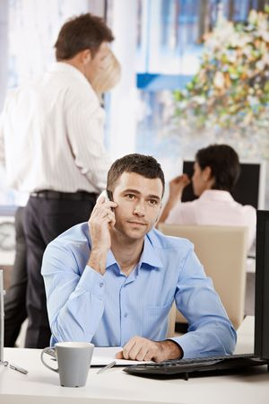 Businessman sitting at desk in office, talking on mobile phone. Stock Photo - 6374251