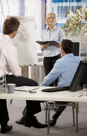 Businesspeople working together in office, Businesswoman presenting idea on whiteboard. photo