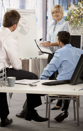 Young businesspeople working together in office, using notebook and whiteboard. photo