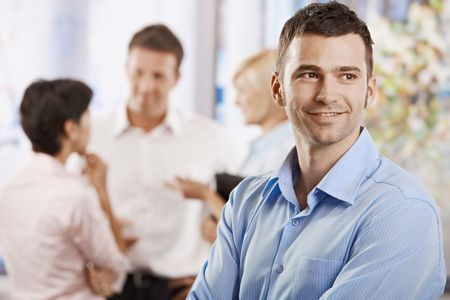Portrait of happy businessman in office, smiling. Colleagues talking in the background. Stock Photo - 6374116