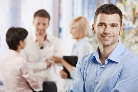 co worker: Portrait of happy businessman in office, smiling. Colleagues talking in the background. Stock Photo