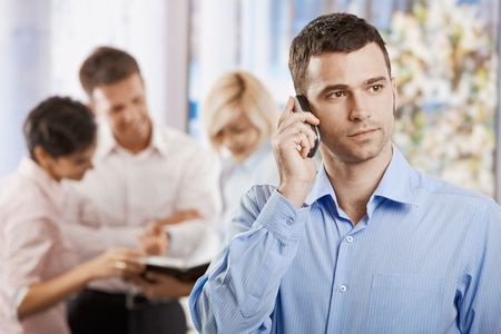 Portrait of serious businessman talking on mobile phone in office. photo