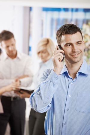 Portrait of smiling businessman talking on mobile phone in office. photo