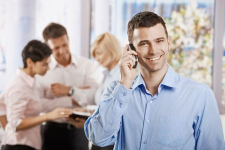 Portrait of happy businessman talking on mobile phone in office, smiling. photo