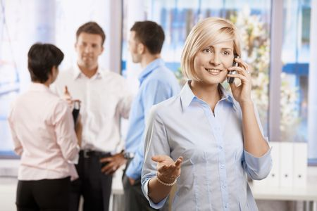 Portrait of happy businesswoman calling in office, smiling. photo