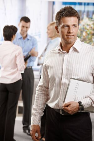 Portrait of businessman in office, holding notepad. Colleagues talking in the background. photo