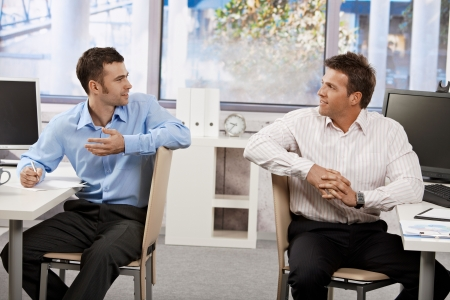 two men talking: Two businessmen sitting at desk in office, looking at each other talking. Stock Photo