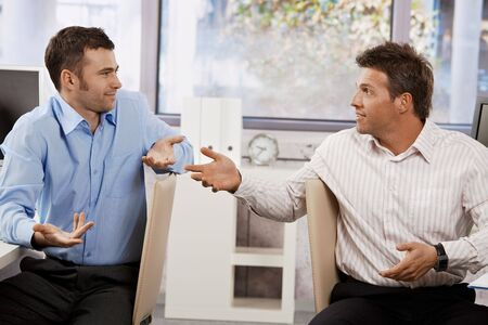 co work: Confused businessmen sitting at desk in office, looking at each other talking. Stock Photo