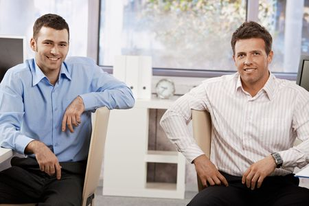 co work: Two happy businessmen sitting at desk in office,  looking at the camera smiling. Stock Photo