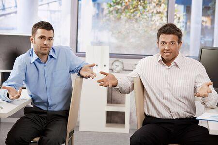 hombre sentado: Dos empresarios, sentado en la Oficina, mirando la c�mara confundidos, manos de speading.