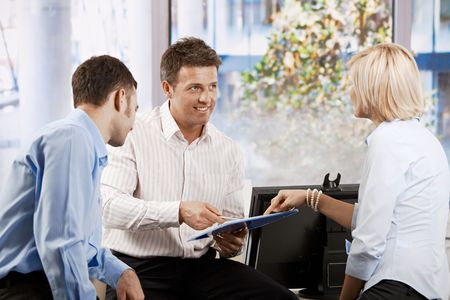 co worker: Business team working in office, people discussing notes in a notepad, smiling. Stock Photo