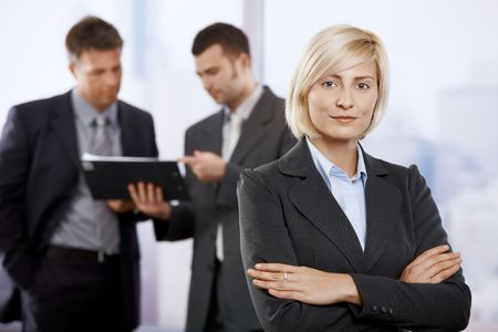 Portrait of young businesswoman in office lobby, smiling. Colleagues talking in the background. Stock Photo - 6374403