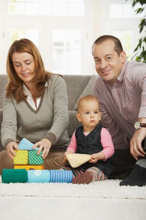 Happy family playing on floor with baby girl at home. photo