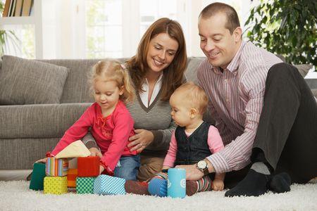 BUEN VIVIR: Familia feliz de cuatro jugando en piso de la sala de estar sentada en el suelo delante del sof�. Foto de archivo
