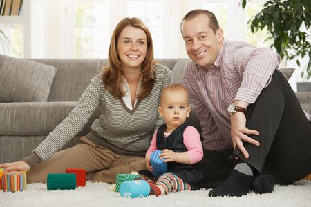 Happy family sitting on floor smiling at camera with baby girl. photo