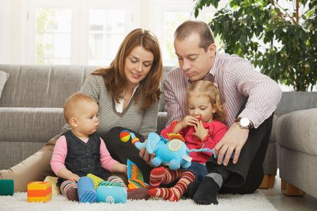 Happy family with two children playing on floor in living room at home sitting on floor in front of sofa. photo