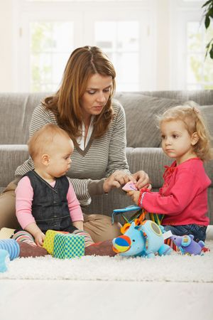 Mum playing on floor with two baby daughters at home. Stock Photo - 6374513