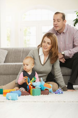 Family fun - Dad, mum and baby daughter playing with toys at home. Stock Photo - 6374531