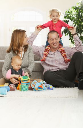 Happy family of four sitting at home on floor of living room, smiling girl sitting in daddys neck. photo