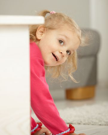 Happy two years old little girl playing peek-a-boo at home smiling. Stock Photo - 6374409