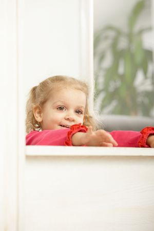 Happy two years old little girl leaning on counter smiling. Stock Photo - 6374405