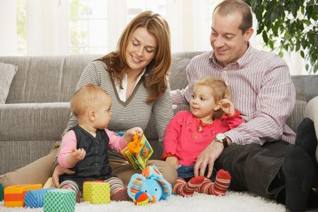 Smiling parents and small daughter looking at baby sitting on floor. Stock Photo - 6374406