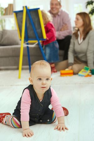 Baby girl crawling on living room floor, family in the background. photo