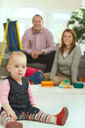 Baby girl sitting in straddle on floor, parents smiling in background. Stock Photo - 6374419
