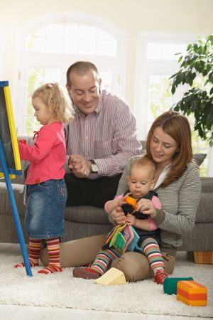 Happy family of four playing in living room smiling. Stock Photo - 6374469