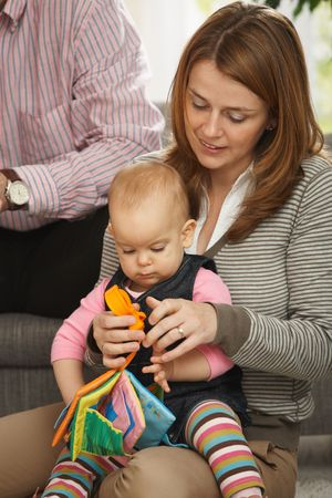 Smiling mother playing with baby girl on floor of sitting room. Stock Photo - 6374482