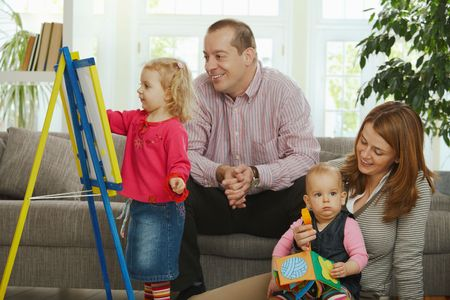 adorable home: Smiling family at home little girl drawing on board.