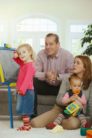 Smiling family looking at camera little girl drawing on board at home. Stock Photo - 6374551