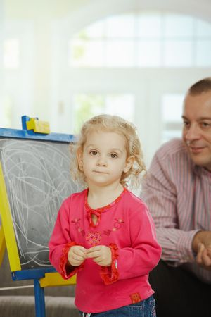 Smiling dad watching small daughter drawing on board at home. photo