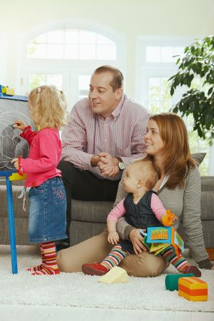 Smiling family looking at little girl drawing on board at home. Stock Photo - 6374426