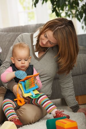 Mum holding baby daughter playing together with toys on living room floor. Stock Photo - 6374514