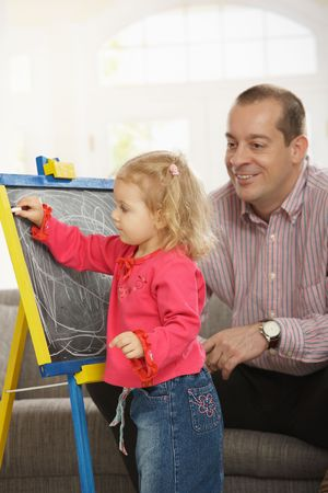 Smiling dad watching small daughter drawing on board at home. Stock Photo - 6374432