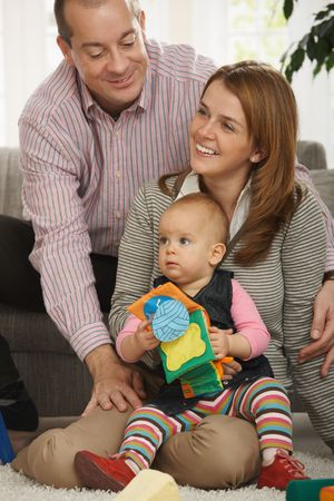 Portrait of happy family of three sitting together in living room. Stock Photo - 6374512