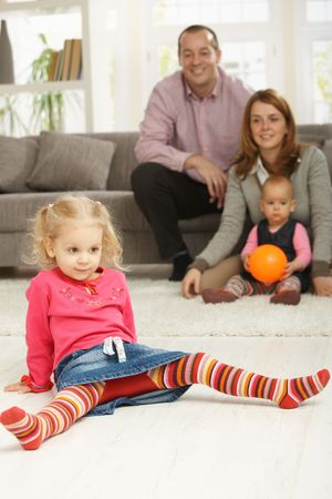 Smiling little girl sitting in straddle on living room floor, with family in background. photo