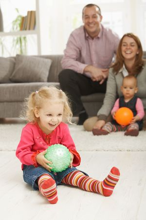 Smiling little girl holding ball at home with laughing family in background. photo