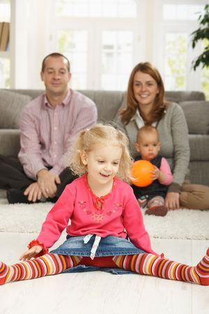 Smiling toddler sitting in straddle on living room floor, with parents and baby sister in background. photo