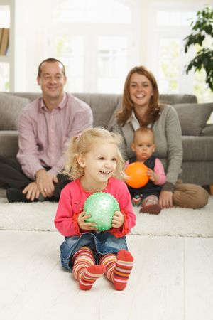Smiling little girl holding ball at home with family in background. photo