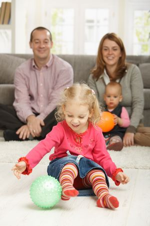 Smiling toddler holding ball with parents and baby in background. photo