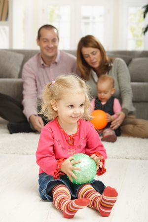 Smiling toddler holding ball with parents and baby in background. Stock Photo - 6374430